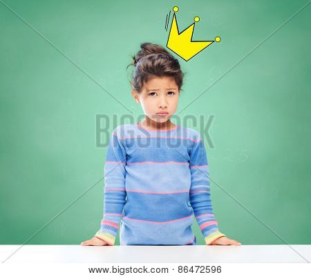 education, people, childhood and emotions concept - sad little school girl over green chalk board background and crown doodle