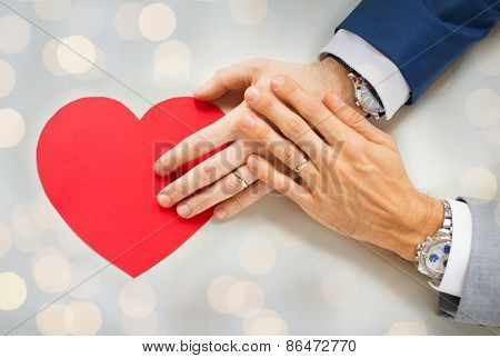 people, homosexuality, same-sex marriage, valentines day and love concept - close up of happy married male gay couple hands with red paper heart shape over holidays lights background