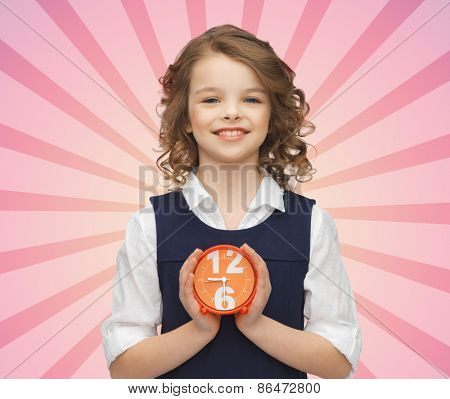 people, childhood, time and punctuality concept - happy girl with alarm clock over pink burst rays background