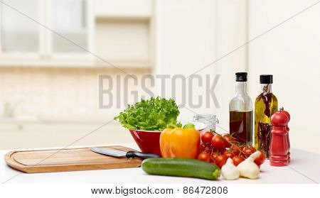 cooking, still life, food and healthy eating concept - fresh ripe vegetables, spices and kitchenware on table over kitchen background