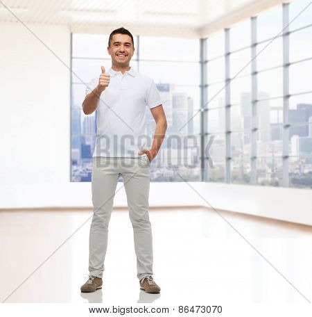 real estate, sale, business, gesture and people concept - smiling man showing thumbs up over empty apartment or office room with big window and city view background