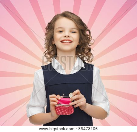 finances, childhood, people, money and savings concept - happy little girl with purse and euro coin over pink burst rays background