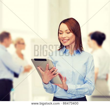 business, internet and technology concept - smiling woman looking at tablet pc computer at office