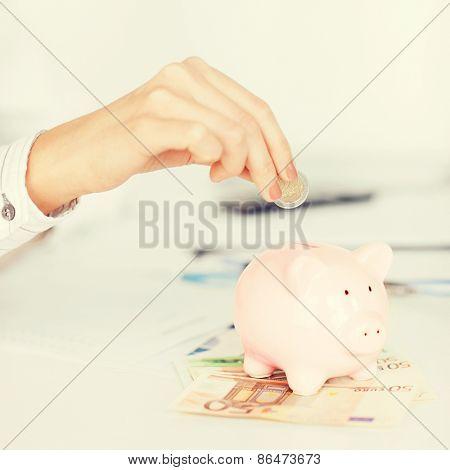business, office, household, school, tax and education concept - woman hand putting coin into small piggy bank