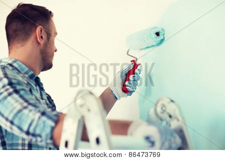 repair, building and home concept - close up of male in gloves holding painting roller
