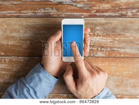 business, education, people and technology concept - close up of male hands holding smartphone and pointing finger to screen on table