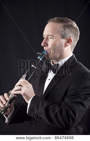 Profile shot of man in tuxedo playing clarinet over black background