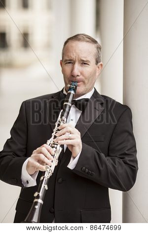 Street performer playing clarinet in tuxedo