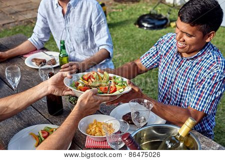 man passing dish healthy fresh salad at outdoor barbecue garden party gathering