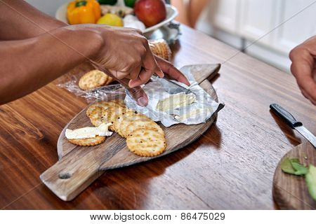 man eat cheese and cracker platter wooden board with knife
