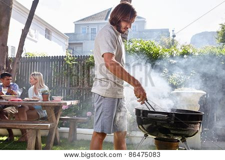 young man preparing fire for friends outdoor barbecue garden party