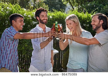 group of friends having outdoor garden party toast with alcoholic beer drinks