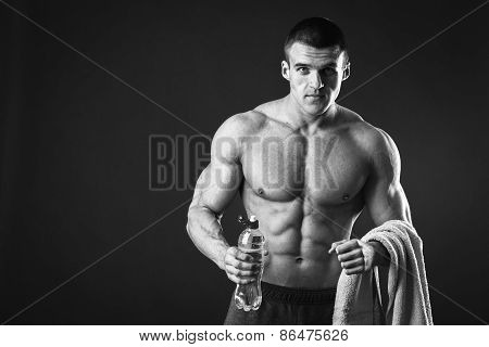 Muscular guy - bodybuilder posing on a gray background