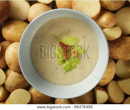 Close up of a potato soup in a pale blue bowl surrounded by potatoes