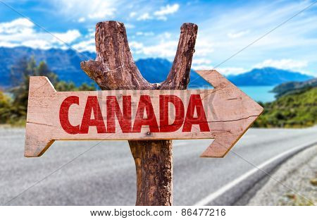 Canada wooden sign with a road background