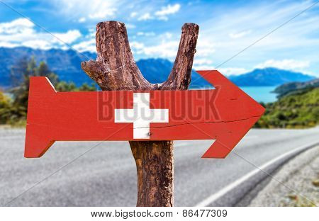 Switzerland wooden sign with a road background