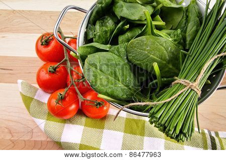 Fresh spinach leaves with tomatoes and strainer