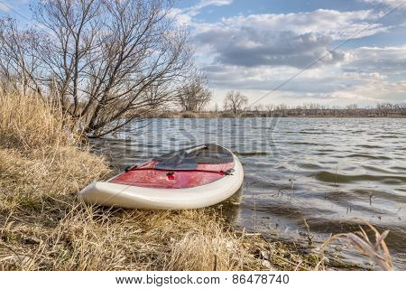 stand up paddleboard with a paddle on alke shore, early spring scenery - start of paddling season concept