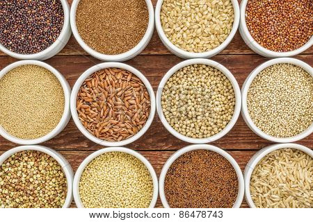 healthy, gluten free grains abstract (quinoa, brown rice, millet, amaranth, teff, buckwheat, sorghum), top view of small round bowls against rustic wood