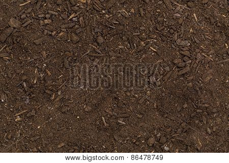 dry organic garden soil background with small wood chips