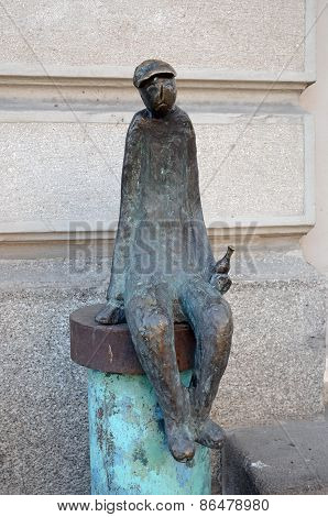 Sculpture of a seated man with a bottle in his hand on the street Rustaveli