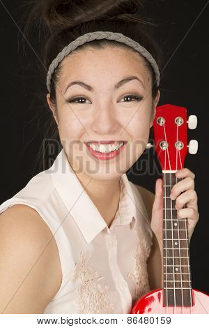 Cute Asian American Teen Girl Holding A Ukulele
