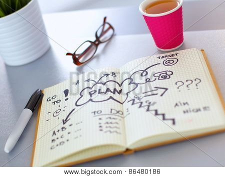 Note book with cup lying on the desk