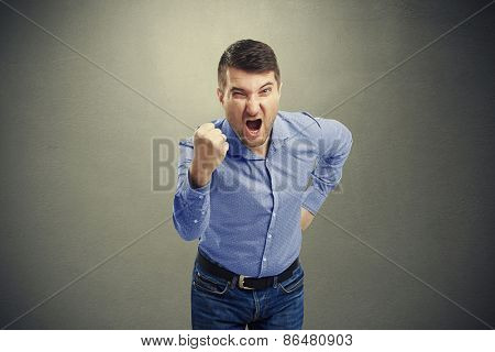 screaming aggressive man showing his fist over dark background