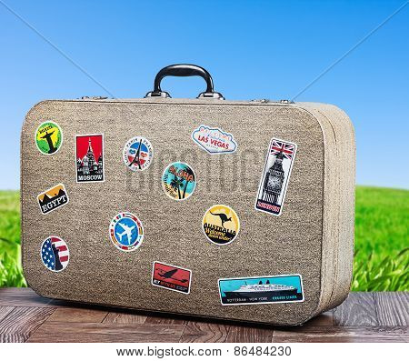 Old Travel Suitcase On Background With Grass Field
