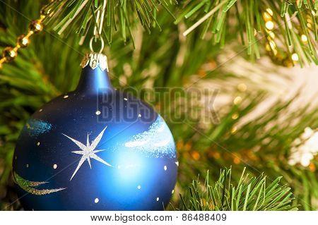Blue Christmas Ball On A Branch Of Artificial Fir