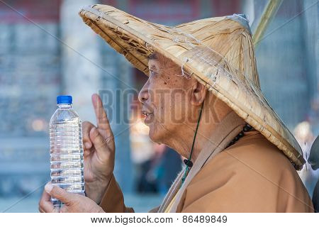 Taiwanese Monk At The Wenwu Temple Blessing A Bottle Of Water