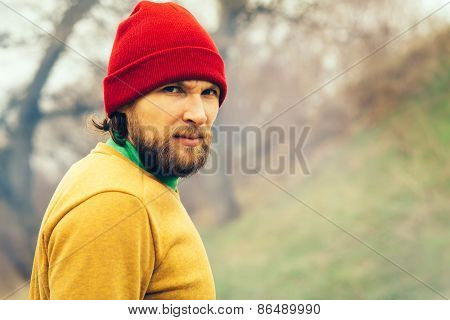 Man Traveler portrait beard face and hat alone in forest