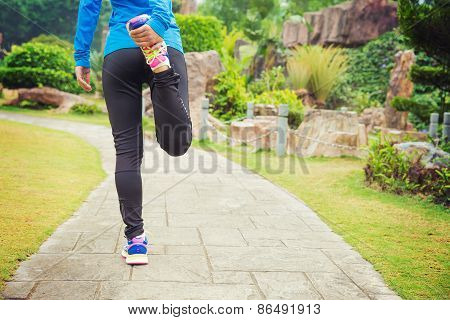 young asian woman warm up before running on fossil forest trail
