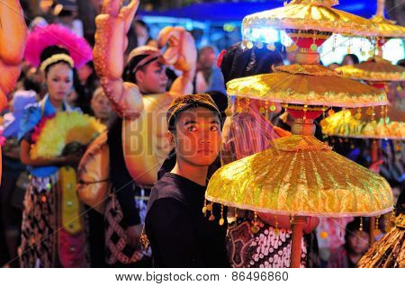 Man holding a traditional umbrella, Yogyakarta city festival parade