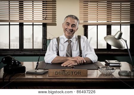 Smiling Vintage Director Sitting At Office Desk
