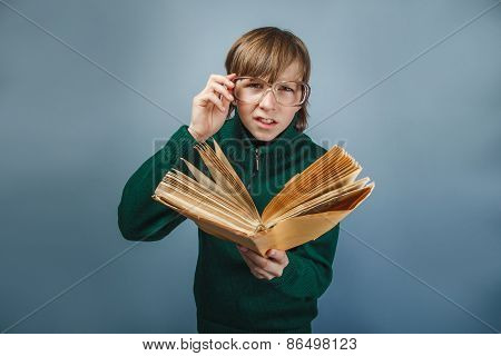 European- looking boy of ten years in glasses  reading  a book o