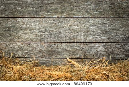 Straw and wheat on a rustic wooden background