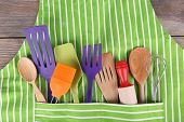 stock photo of apron  - Set of kitchen utensils in pocket of apron - JPG