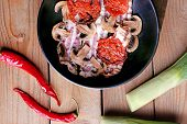 foto of bacon strips  - Strips of bacon with sliced mushrooms and tomato in pan on wooden planks background - JPG