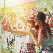 picture of selfie  - Two happy teenage girlfriends in modern colorful clothes taking a selfie on sunny summer day against colorful painted wall.