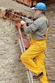 foto of chisel  - Construction worker demolishing brick wall with electric plugger chisel hammer tool - JPG