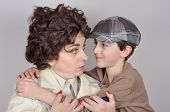 picture of newsboy  - Smiling son with tartan newsboy cap hugging his surprised and angry mother - JPG