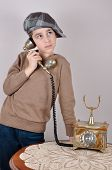 stock photo of newsboy  - Cute thoughtful young boy with tartan newsboy cap talking on the retro telephone - JPG