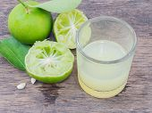 stock photo of juices  - Close up lemon juice with sliced lemon squeezed  - JPG