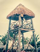 foto of lifeguard  - Lifeguard hut with thatched roof on Mexican shore - JPG