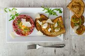 foto of tartar  - Beef tartar and toast bread with garlic sprinkled with parmesan shavings and microgreens - JPG