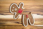 stock photo of gingerbread man  - holiday cookie a gingerbread man broken in half with a scared expression - JPG