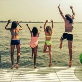 stock photo of pier a lake  - Friends jumping off the pier into Lake Wawasee - JPG