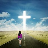 picture of rear-end  - Backside view of teenage girl walking on the highway toward a cross on the end of the road - JPG
