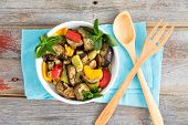 foto of brinjal  - Healthy bowl of succulent Turkish grilled vegetables with eggplant zucchini red and yellow bell peppers and fresh sprigs of mint on a blue napkin on a rustic wooden table - JPG
